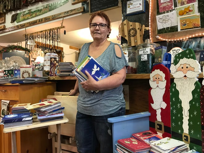 Bonnie Suemnicht at the Maple Tree with some of the 14,000 cards they've received this year that they will send to troops through the A Million Thanks organization.