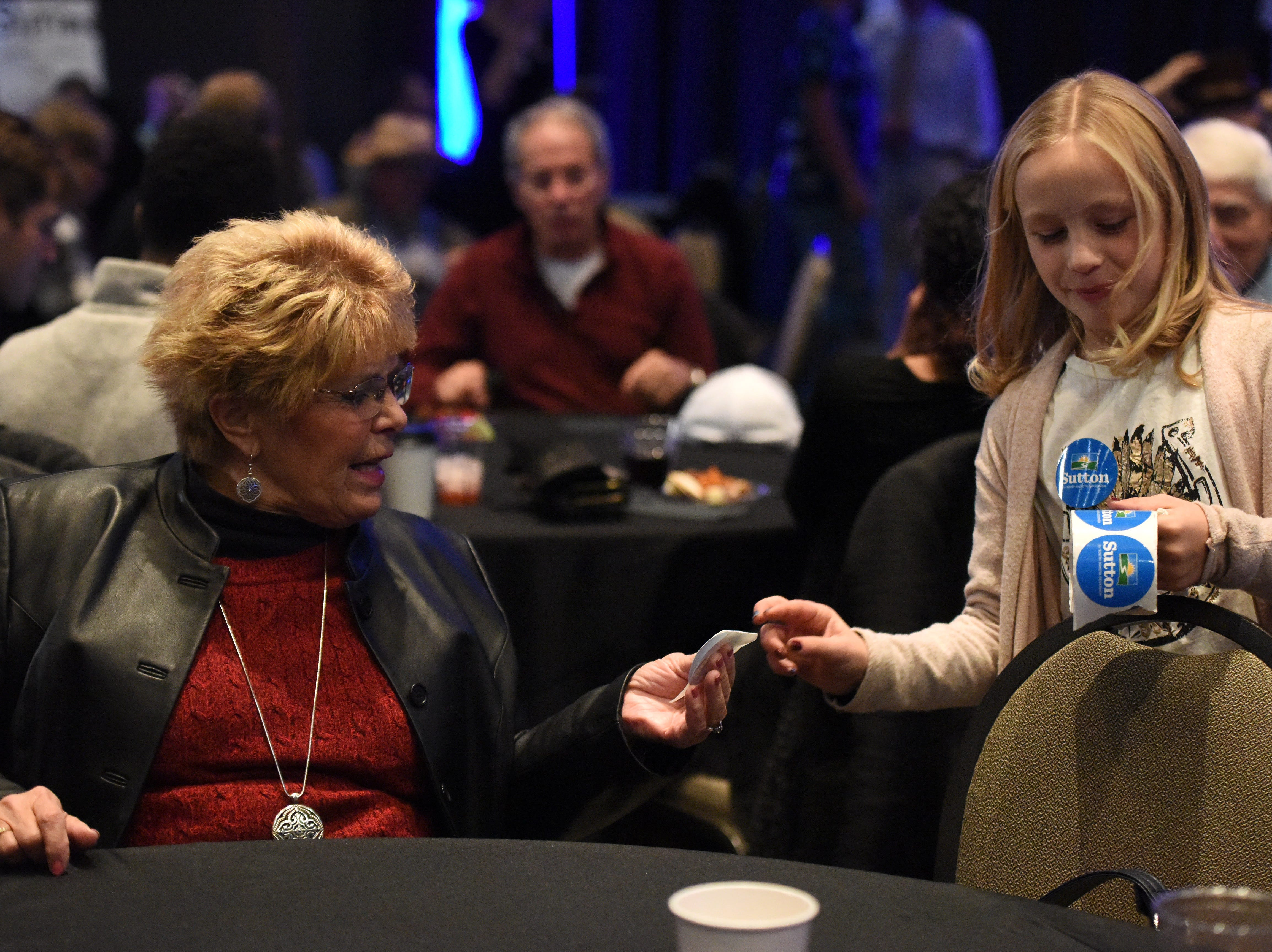 Adessa Hansen, 9, hands a Billie Sutton sticker to Jennifer Ortman at the Democratic night party, Tuesday, Nov. 6, 2018 at The District in Sioux Falls, S.D.