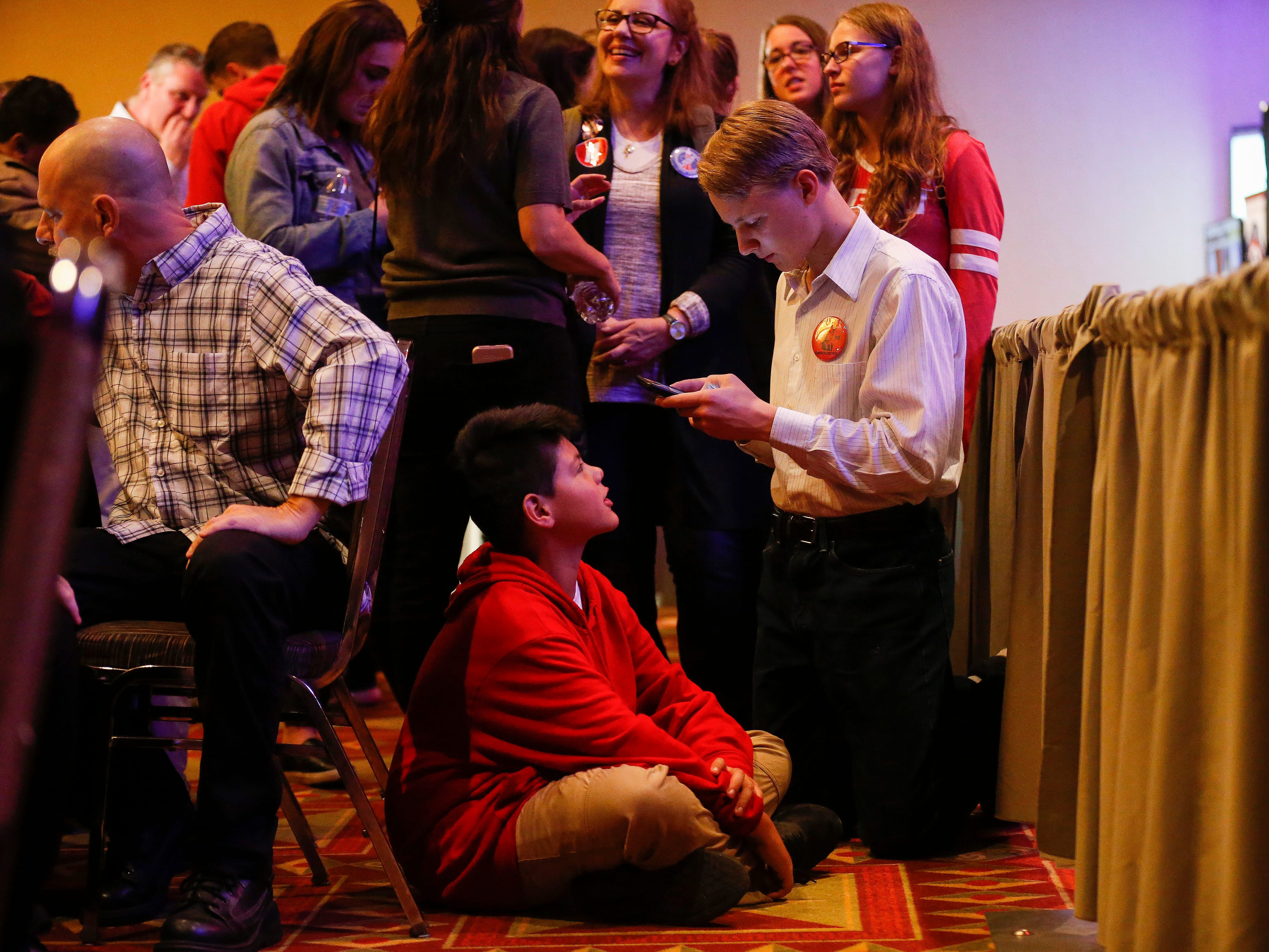 Adrik Fisher, 16, right, and Zachariah Lynch, 11, check as results come in at the Greene County Republican's watch party at the University Plaza hotel on Tuesday, Nov. 6, 2018.