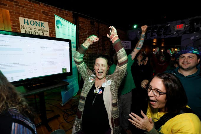 Amy Powell, left, and Ann Siegel, right, react to a win for Amendment 2 at the New Approach Missouri watch party at Riad in downtown Springfield on Tuesday, Nov. 6, 2018.