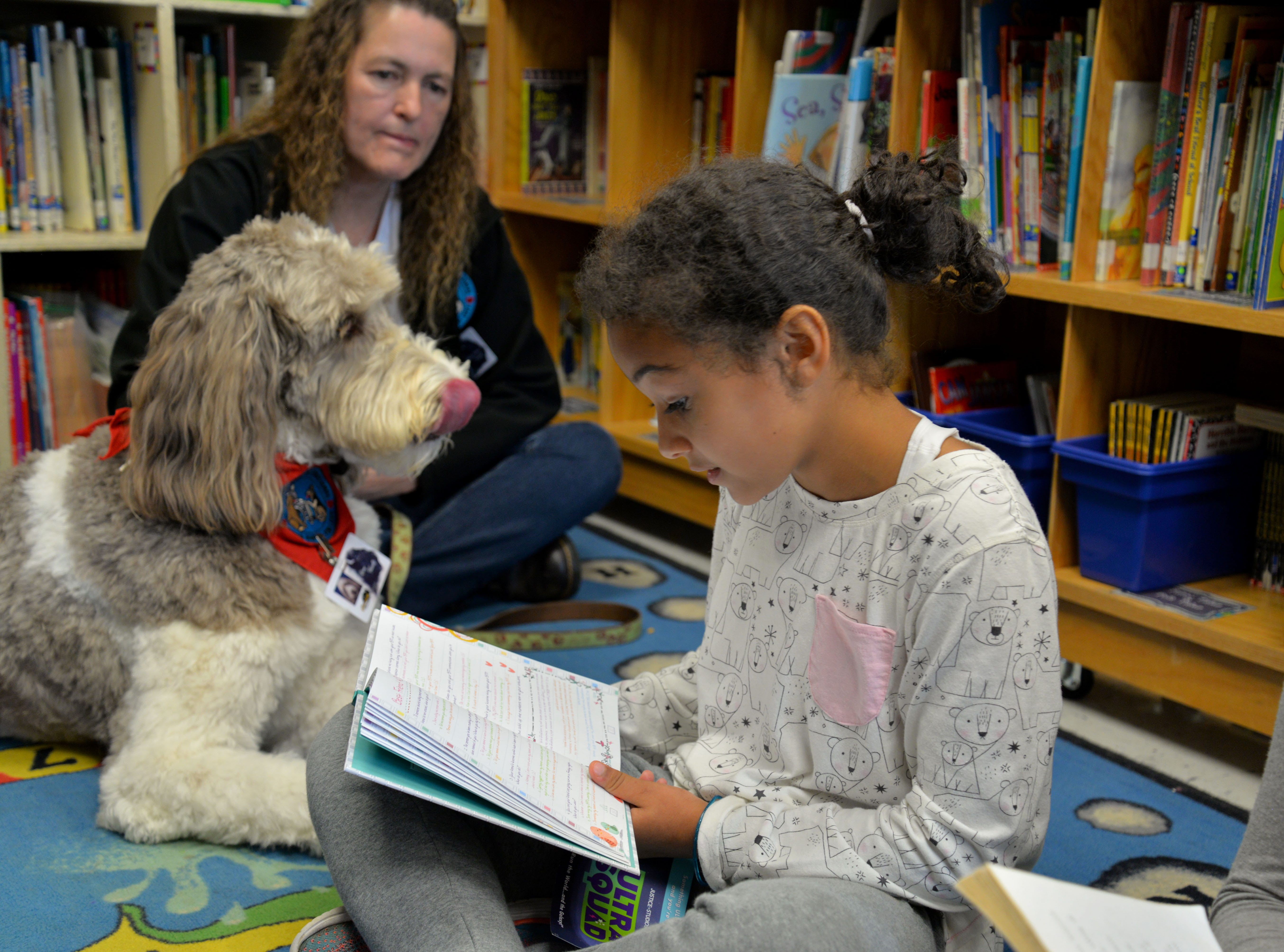 Kathleen Wilson and her labradoodle, Rory, visit Churchville Elementary once a week so students can read to the dog. Rory is a certified therapy dog and is allowed in any Augusta County School or school function. Here Rory is pictured with Charli Cairns, 8 years old.