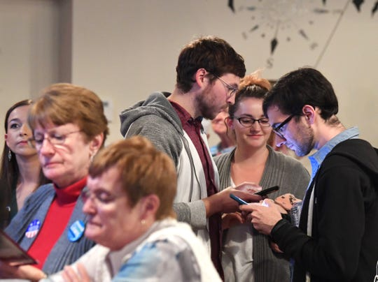 Several in attendance use their phones to keep track of election results while at an election night watch party in Waynesboro on Tuesday, Nov. 6, 2018.