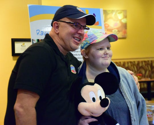 Raegan Fitzgerald, right, of Staunton poses with the Mickey Mouse stuffed doll given to her by Frank Squeo, left, founder of Baking Memories 4 Kids, after being given a one-week, all-expenses-paid trip to the Orlando, Fla., theme parks, including Disney World, by the charity. Fitzgerald was diagnosed with acute Lymphoblastic Leukemia less than a year ago.