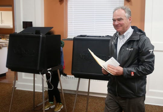 Sen. Tim Kaine, D-Va., carries his ballot to the vote counting machine as he votes in Richmond, Va., Tuesday, Nov. 6, 2018. Kaine is running against Republican Corey Stewart.