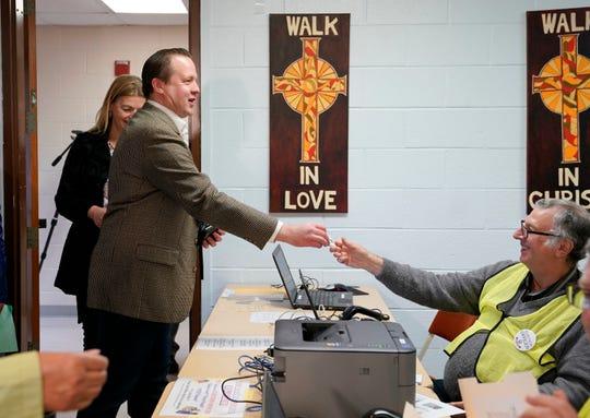 Virginia Republican senatorial candidate Corey Stewart presents a photo-id as he checks in to vote at St. Margaret's Episcopal Church in Woodbridge, Va., Tuesday, Nov. 6, 2018.