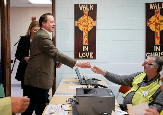 Virginia Republican senatorial candidate Corey Stewart presents a photo-id as he checks in to vote at St. Margaret's Episcopal Church in Woodbridge, Va., Tuesday, Nov. 6, 2018.