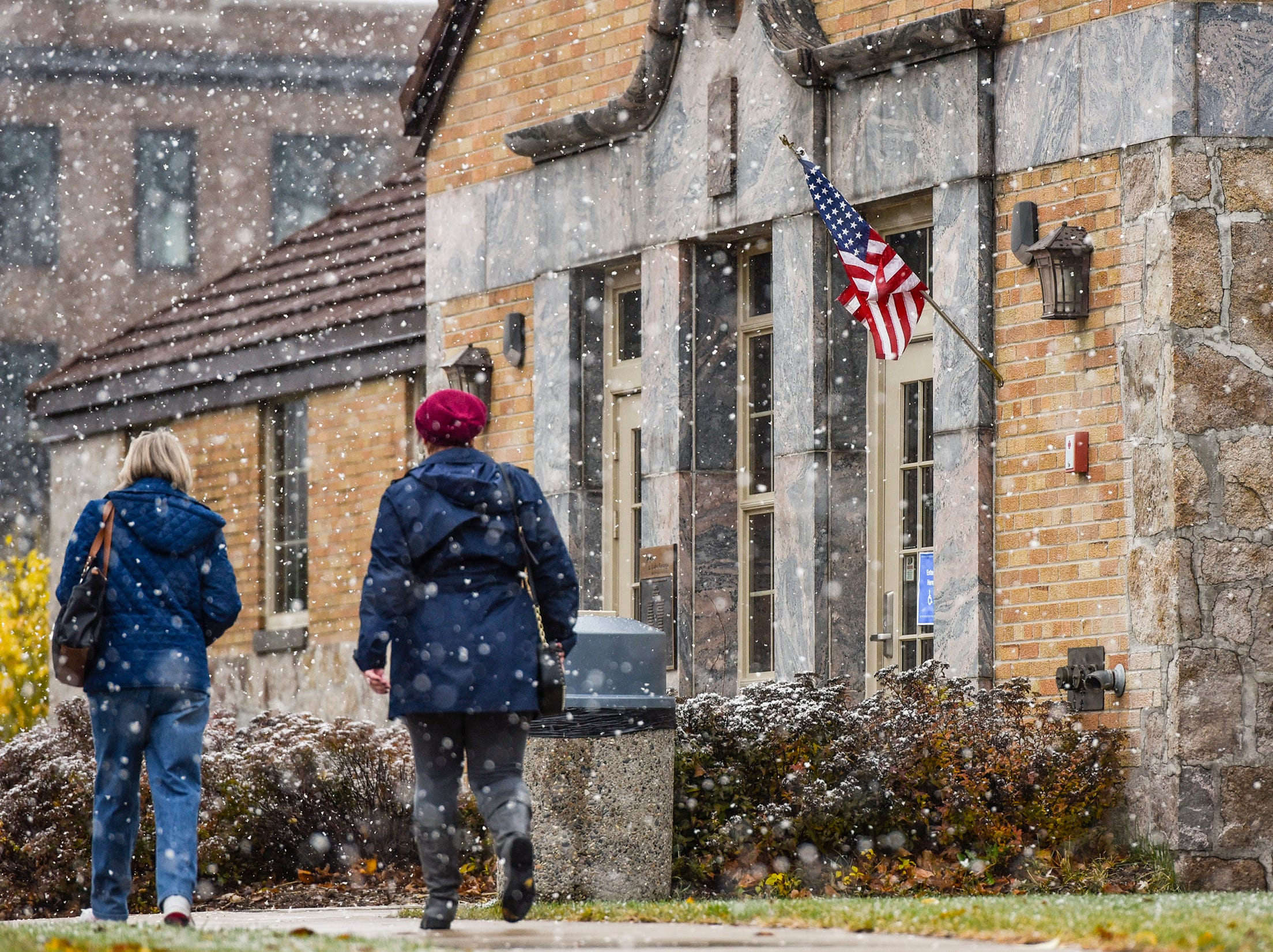 Snow started to fall as voters walk to the Lake George Municipal Complex Tuesday, Nov. 6, in St. Cloud.