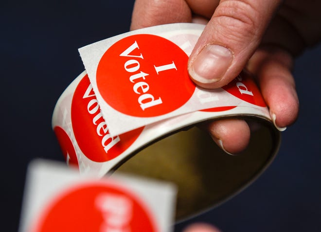"""Voters get their """"I Voted"""" sticker after casting their ballot Tuesday, Nov. 6, St. Cloud State University."""