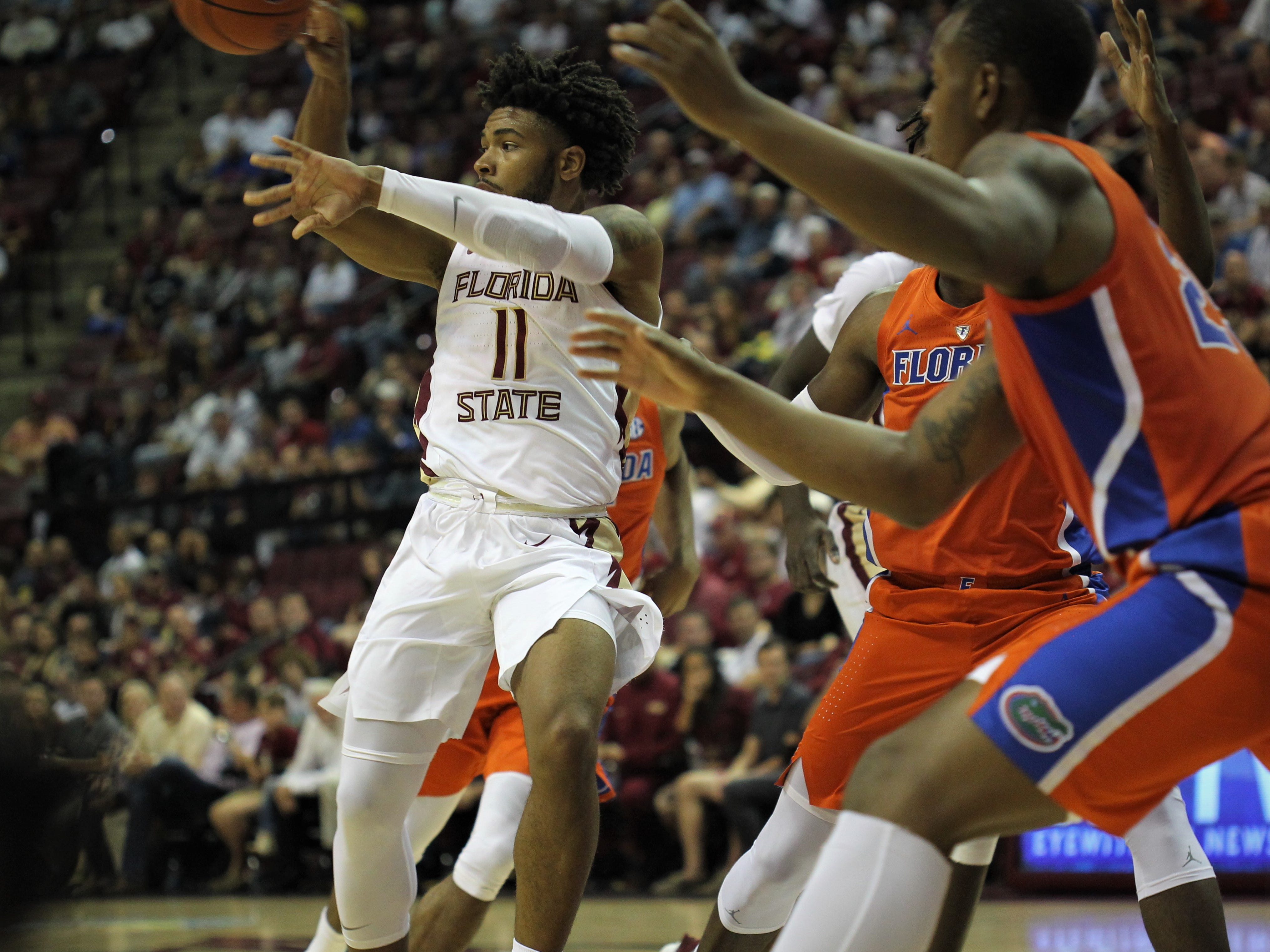 Florida State's David Nichols makes a pass off a dribble-drive during the Sunshine Showdown game against Florida on Tuesday at the Tucker Civic Center.