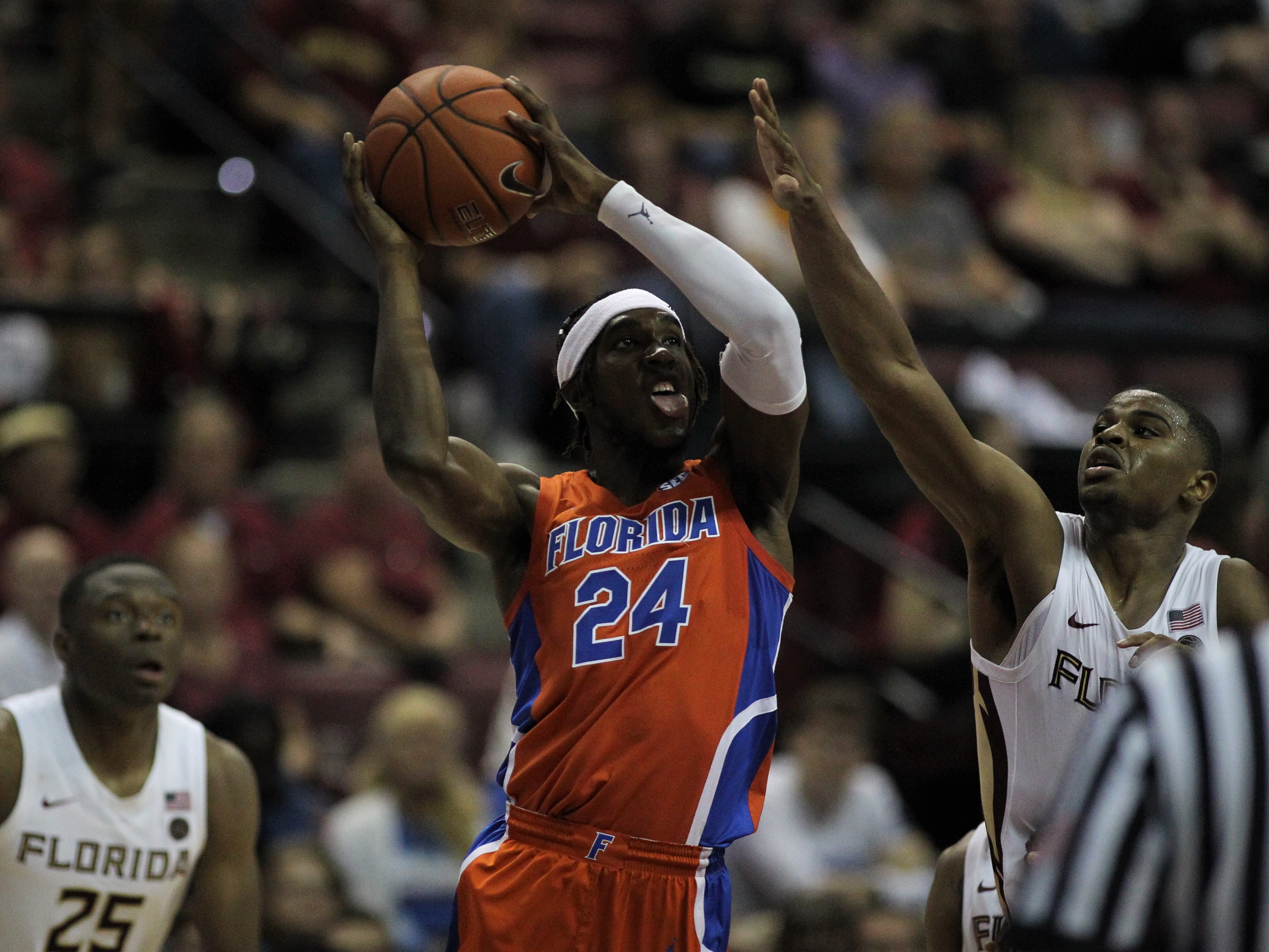 Florida's Deaundrae Ballard goes up for a layup as FSU's M.J. Walker contests during the Sunshine Showdown game Tuesday at the Tucker Civic Center.