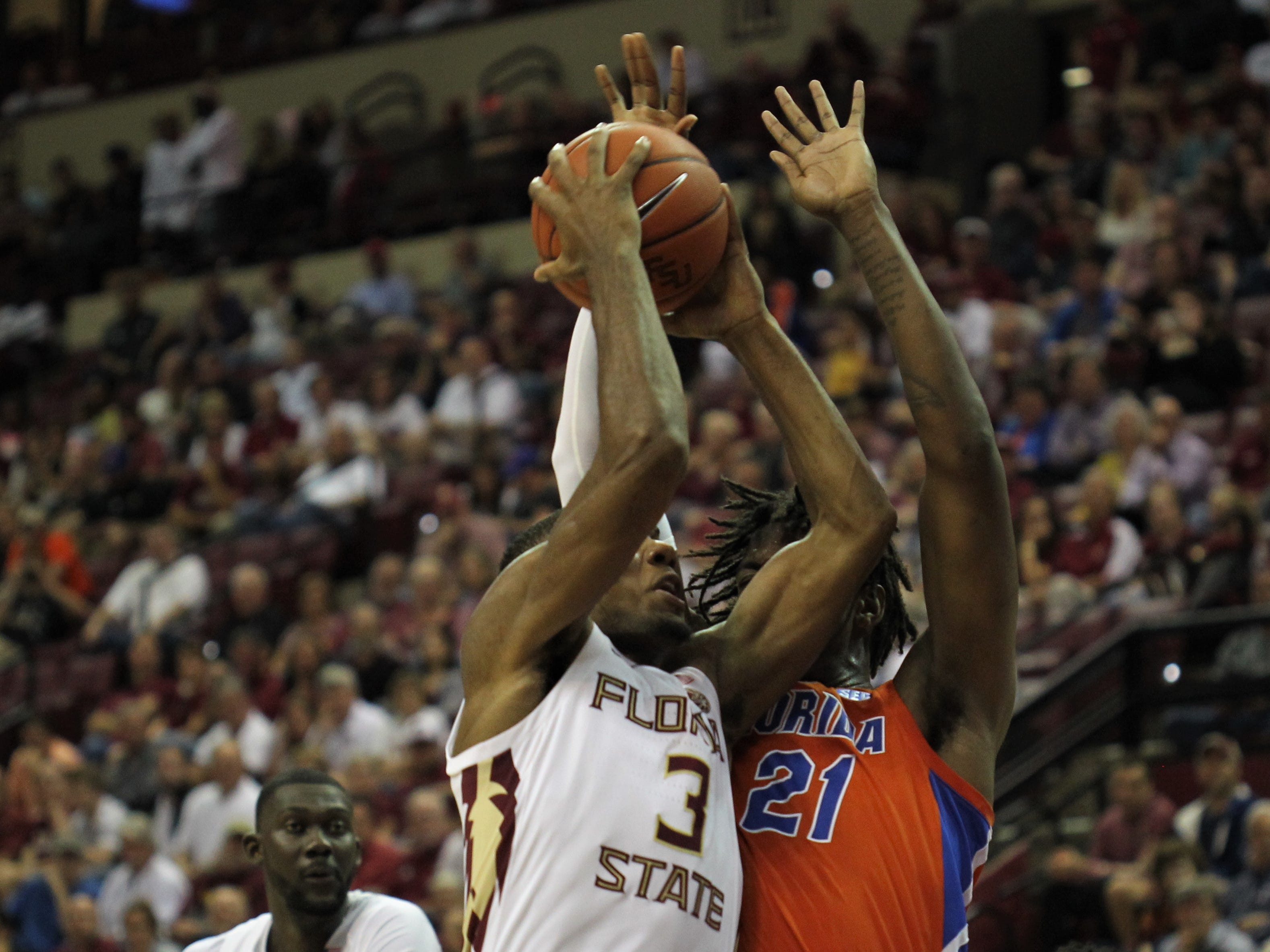 Florida State's Trent Forrest goes up for a basket against Florida's Dontay Bassett during the Sunshine Showdown game Tuesday at the Tucker Civic Center.
