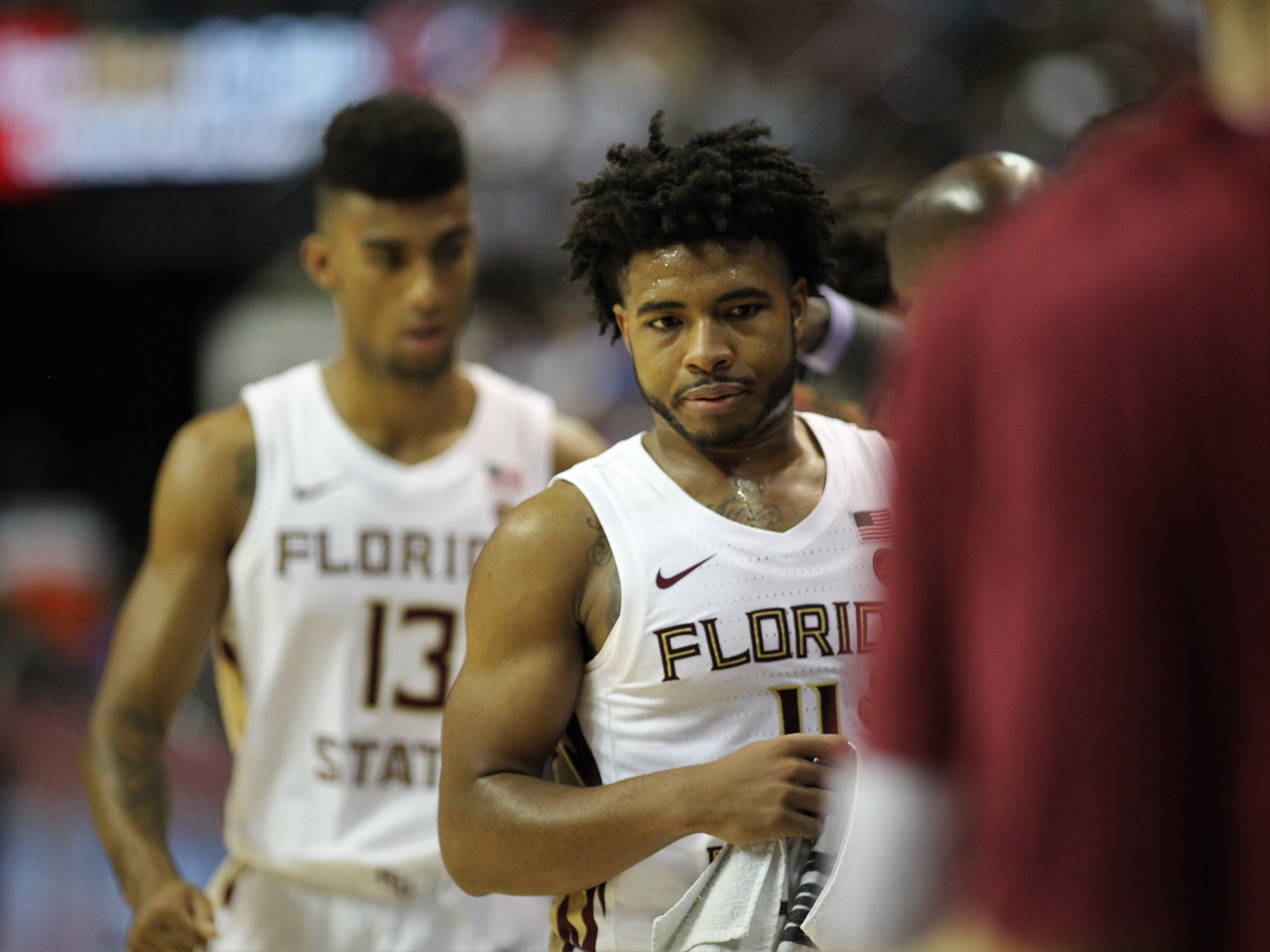 Florida State's David Nichols (11) and Anthony Polite (13)  head to the bench after successful minutes during the Sunshine Showdown game against Florida on Tuesday at the Tucker Civic Center.
