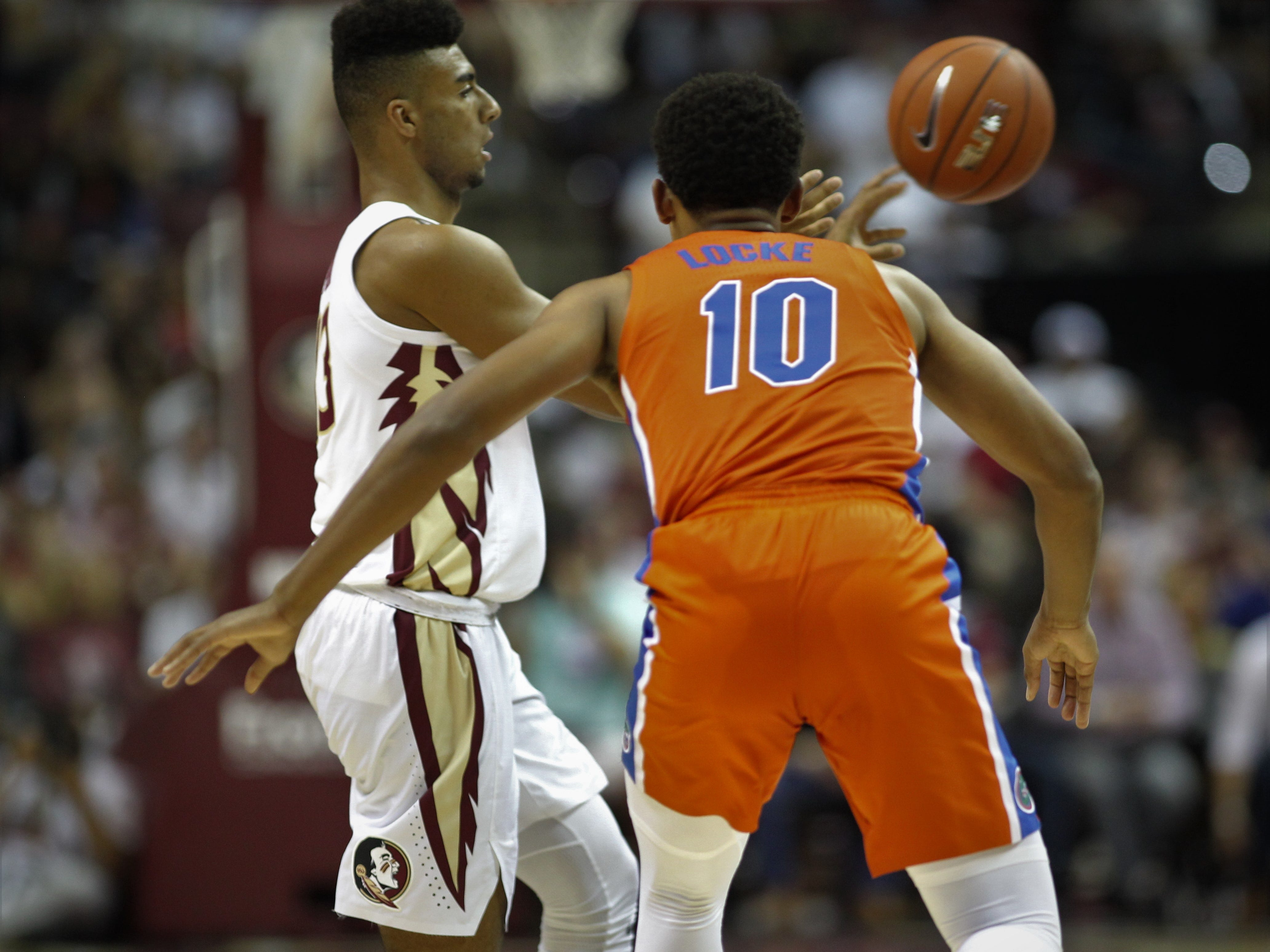 Florida State's Anthony Polite makes a pass around the perimeter as Florida's Noah Locke defends during the Sunshine Showdown game Tuesday at the Tucker Civic Center.