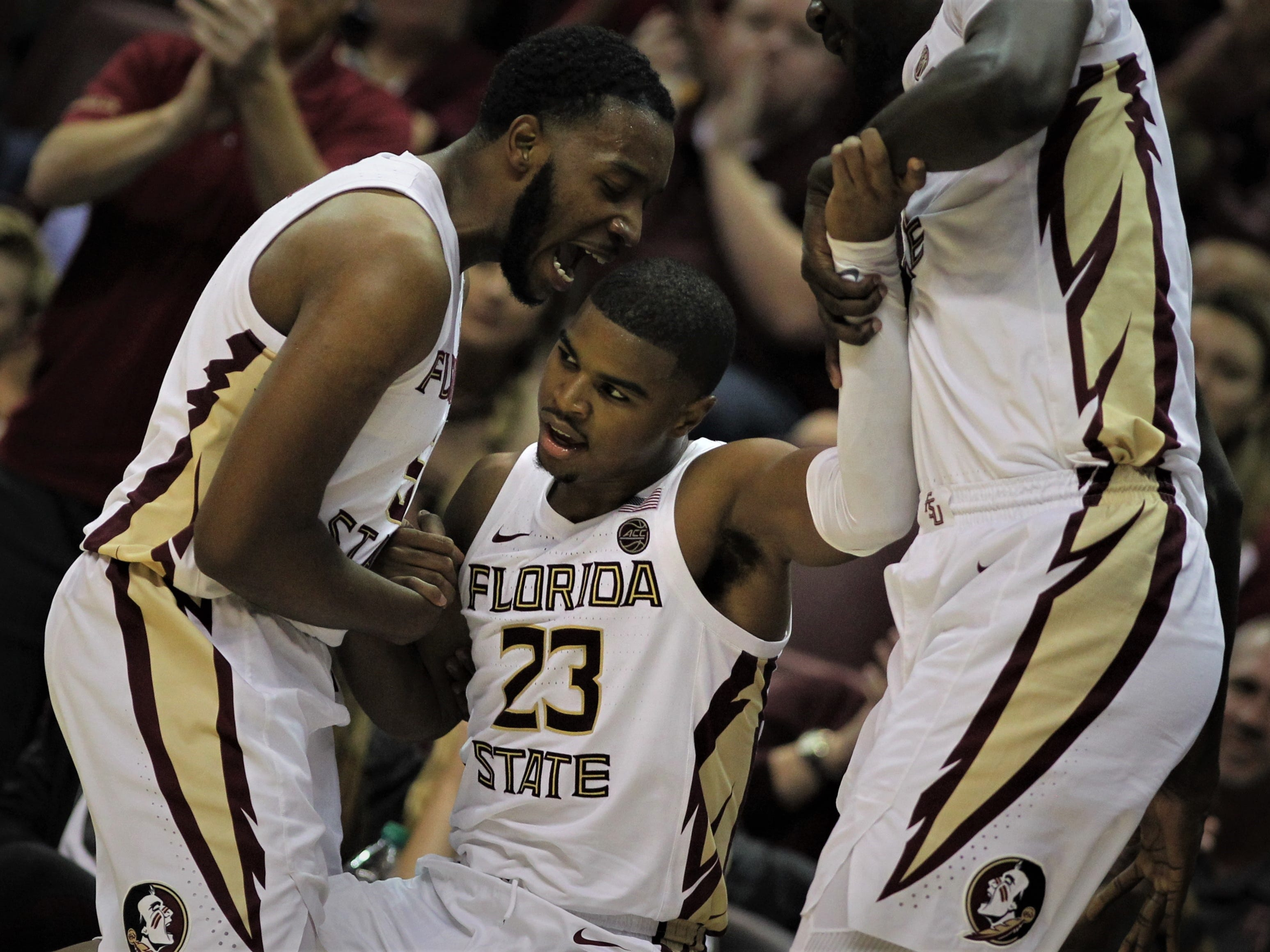 Florida State's M.J. Walker is helped up by P.J. Savoy and Christ Koumadje after making a 3-pointer while getting fouled by Florida during the Sunshine Showdown game Tuesday at the Tucker Civic Center.