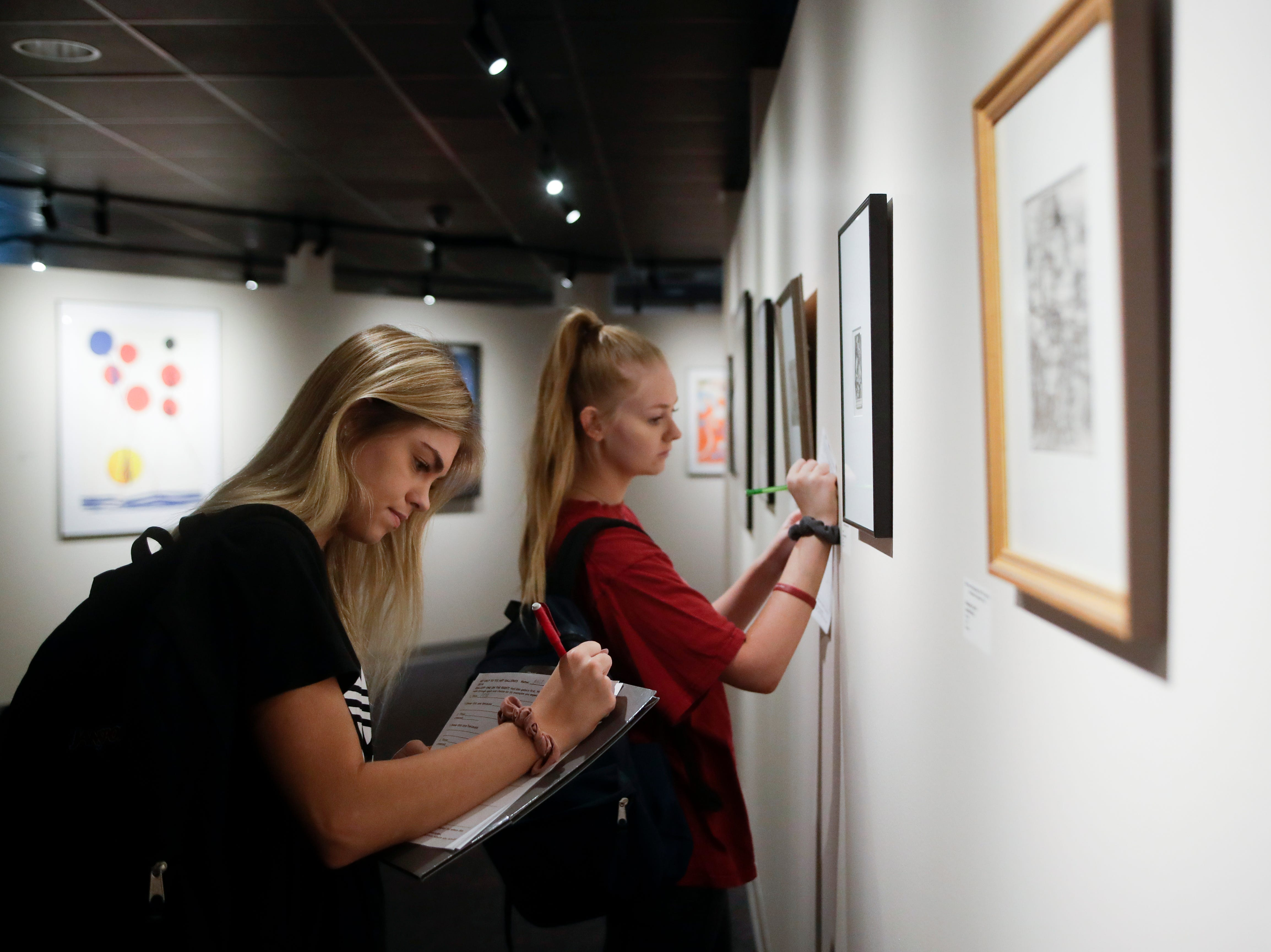 "Tallahassee Community College students Alise Singletary, left and Meagan Kenney work on an assignment for a humanities class by taking observations about pieces in the exhibit ""500 Years of Printmaking: the FSU Collection"" on display now in the TCC Fine Arts Gallery on the TCC campus."