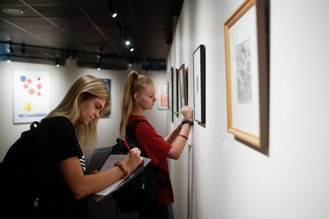 """Tallahassee Community College students Alise Singletary, left and Meagan Kenney work on an assignment for a humanities class by taking observations about pieces in the exhibit """"500 Years of Printmaking: the FSU Collection"""" on display now in the TCC Fine Arts Gallery on the TCC campus."""
