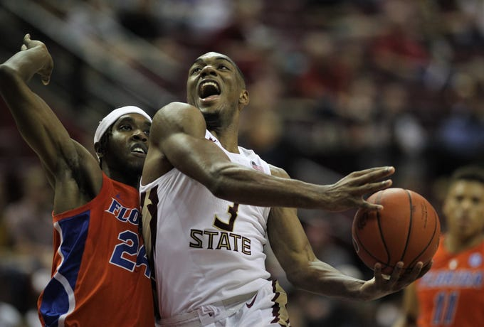 Florida State's Trent Forrest drives in for a layup as Florida's Deaundrae Ballard defends during the Sunshine Showdown game Tuesday at the Tucker Civic Center.
