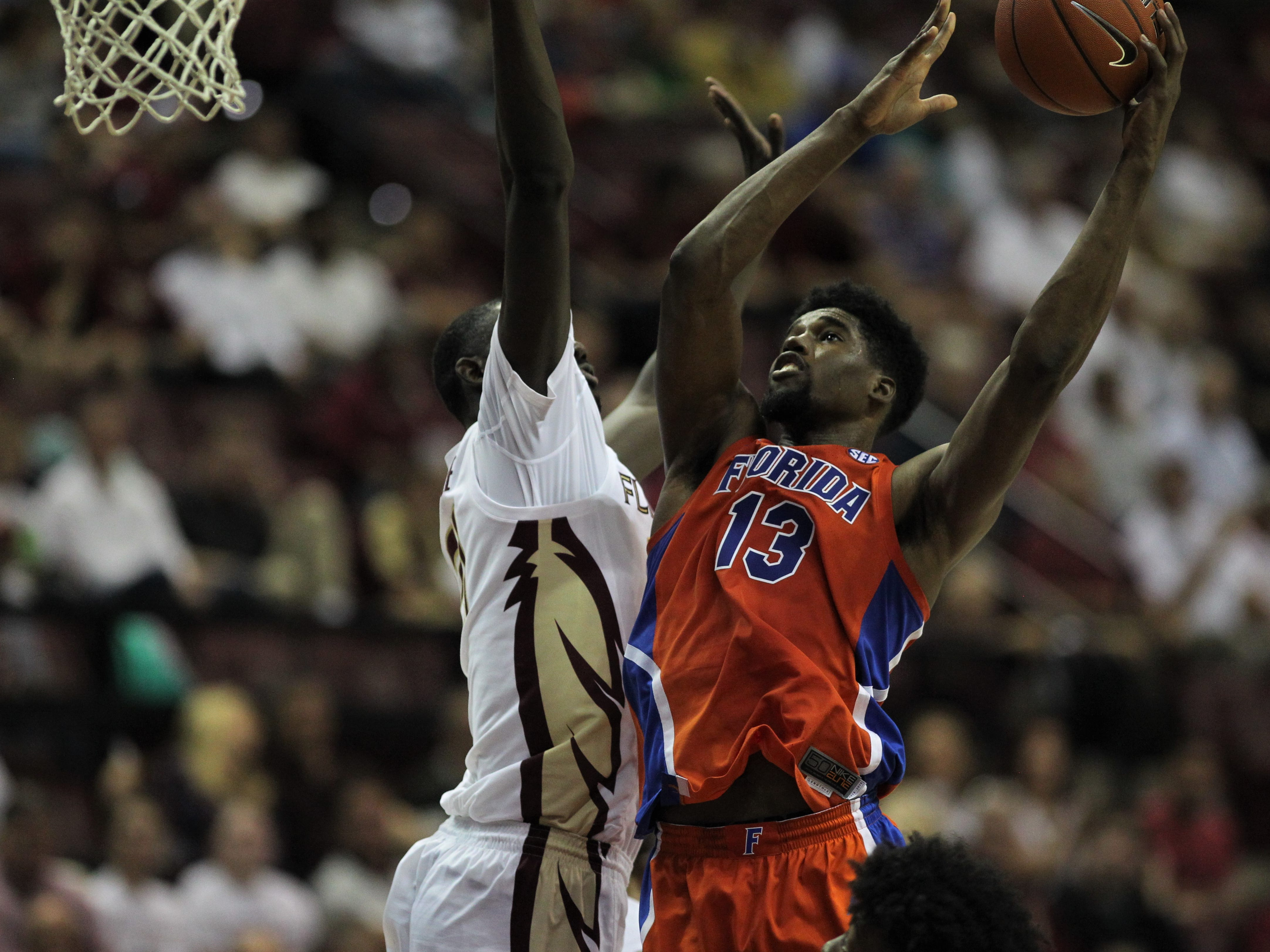 Florida's Kevarrius Hayes goes up for a contested layup by FSU's Christ Koumadje during the Sunshine Showdown game Tuesday at the Tucker Civic Center.