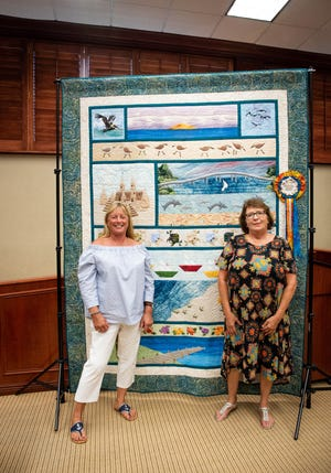 "Sunbonnet Sue Quilt Guild recently unveiled the Centennial Quilt to Vero Beach City Council. Cindy Baron, left, and Diane Miller stand in front of the king-sized quilt, named ""A Day at the Beach - Vero Beach Centennial Quilt,"" which will be raffled off at the ""Treasures of the Treasure Coast"" quilt show on Feb. 7-9 at the Indian River County Fairgrounds."