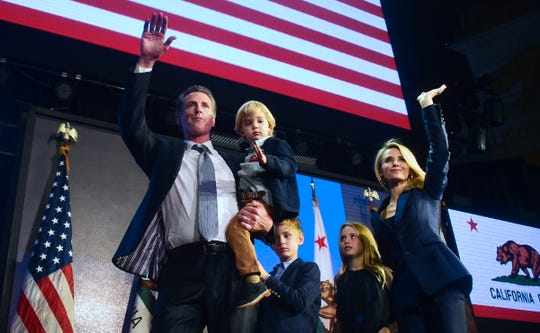 California's Gov.-elect Gavin Newsom and his family wave to supporters from the stage at his election night watch party in Los Angeles late Tuesday night.