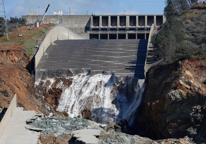 In this Feb. 28, 2017, file photo, water flows down the Oroville Dam's crippled spillway.