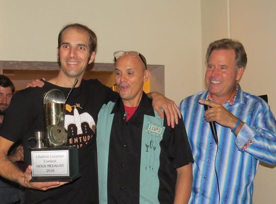 Bartenders Sam Gay, left, of the Ojai Valley Inn, and Elvis Rivers, of Ventiki, center, celebrate their Libation Creation Judges Choice win with event emcee Mike Donohue.