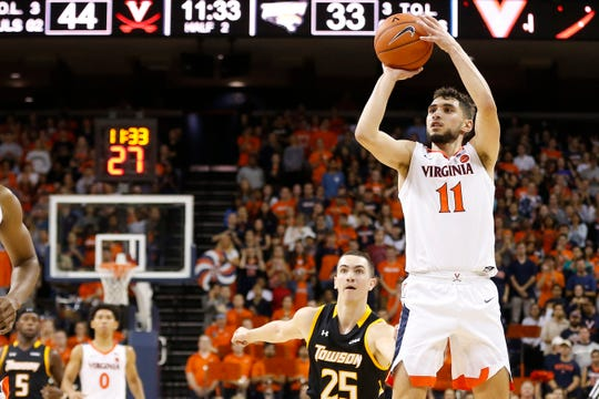 Virginia Cavaliers guard Ty Jerome (11) shoots the ball as Towson Tigers guard Nicolas Timberlake (25) looks on in the second half at John Paul Jones Arena.