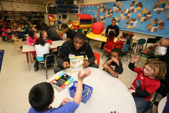 Nyack College basketball player Justin Best reads a book to the kindergarten students at the Upper Nyack Elementary School in January 2014.