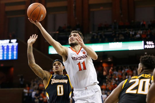Virginia Cavaliers guard Ty Jerome (11) shoots the ball as Towson Tigers guard Tobias Howard (0) defends in the second half at John Paul Jones Arena.