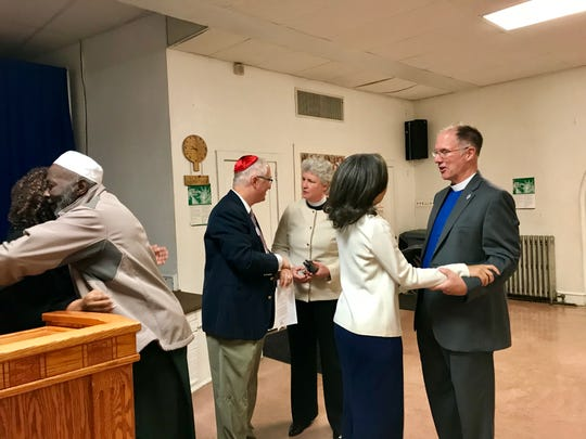 Rabbi Michael Beals, center, and other faith leaders in Wilmington greet each other before a prayer session addressing anti-Semitism at the Bethel African Methodist Episcopal Church