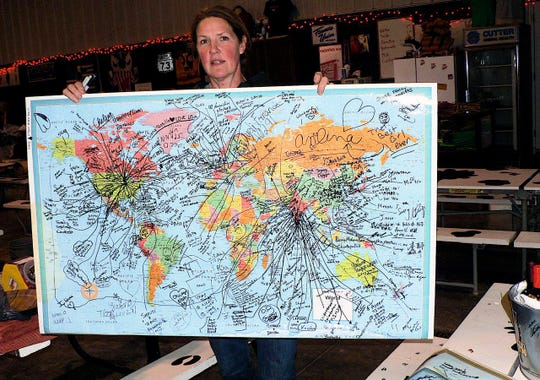 Tina Hinchley holds a map showing the homes of this years international visitors to the farm.