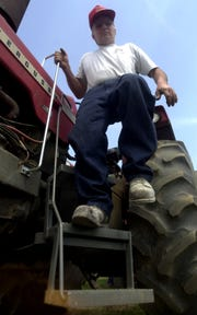 Jim Zell, town of Mosinee, demonstrates his three-step tractor  made by Dave Welock, Marathon during AgrAbility Field Day at Zell's farm in 1999.  Zell suffered a back injury in 1988 and later made changes to his tractors and other equipment.