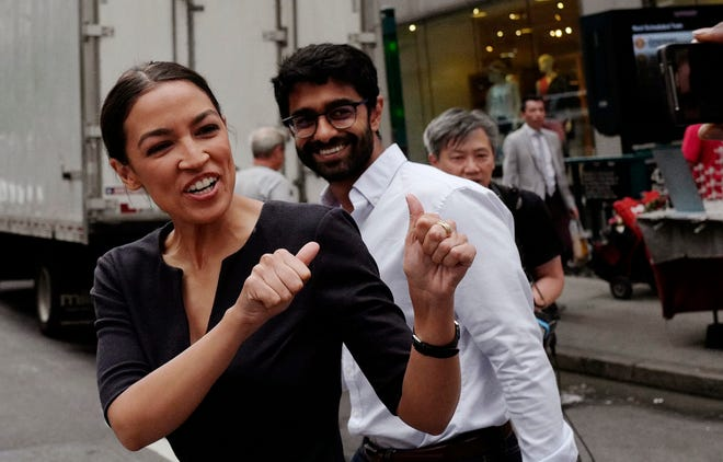 Alexandria Ocasio-Cortez, the winner of a Democratic Congressional primary in New York, greets a passerby in New York, Wednesday, June 27, 2018, the morning after she upset U.S. Rep. Joe Crowley in Tuesday's primary election.