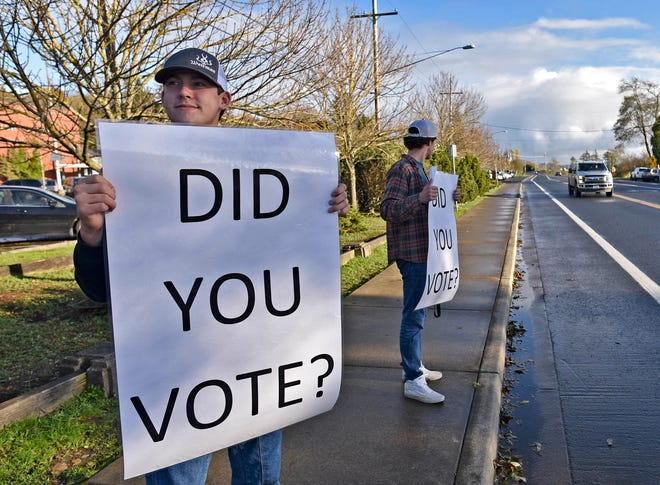 Burke Matthews, left, and Josh Shipley hold up signs in front of Astoria High School in Astoria, Ore., on Election Day.