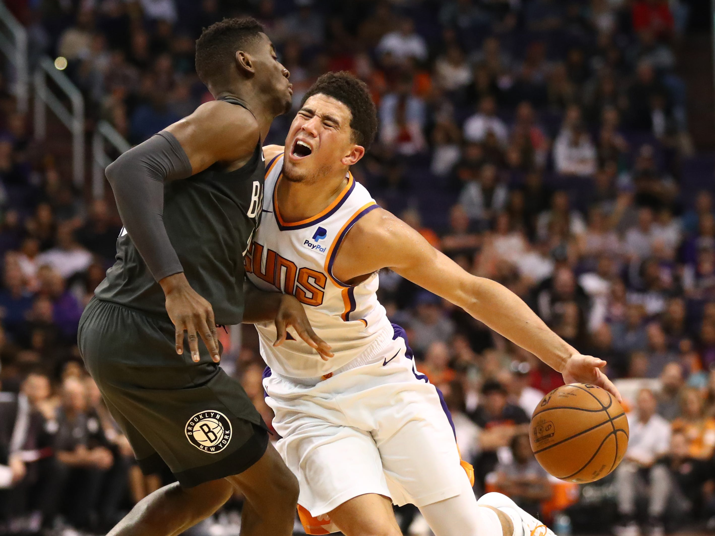 Nov. 6: Suns guard Devin Booker (1) collides with Nets defender Caris LeVert (22) during the second half in Phoenix.