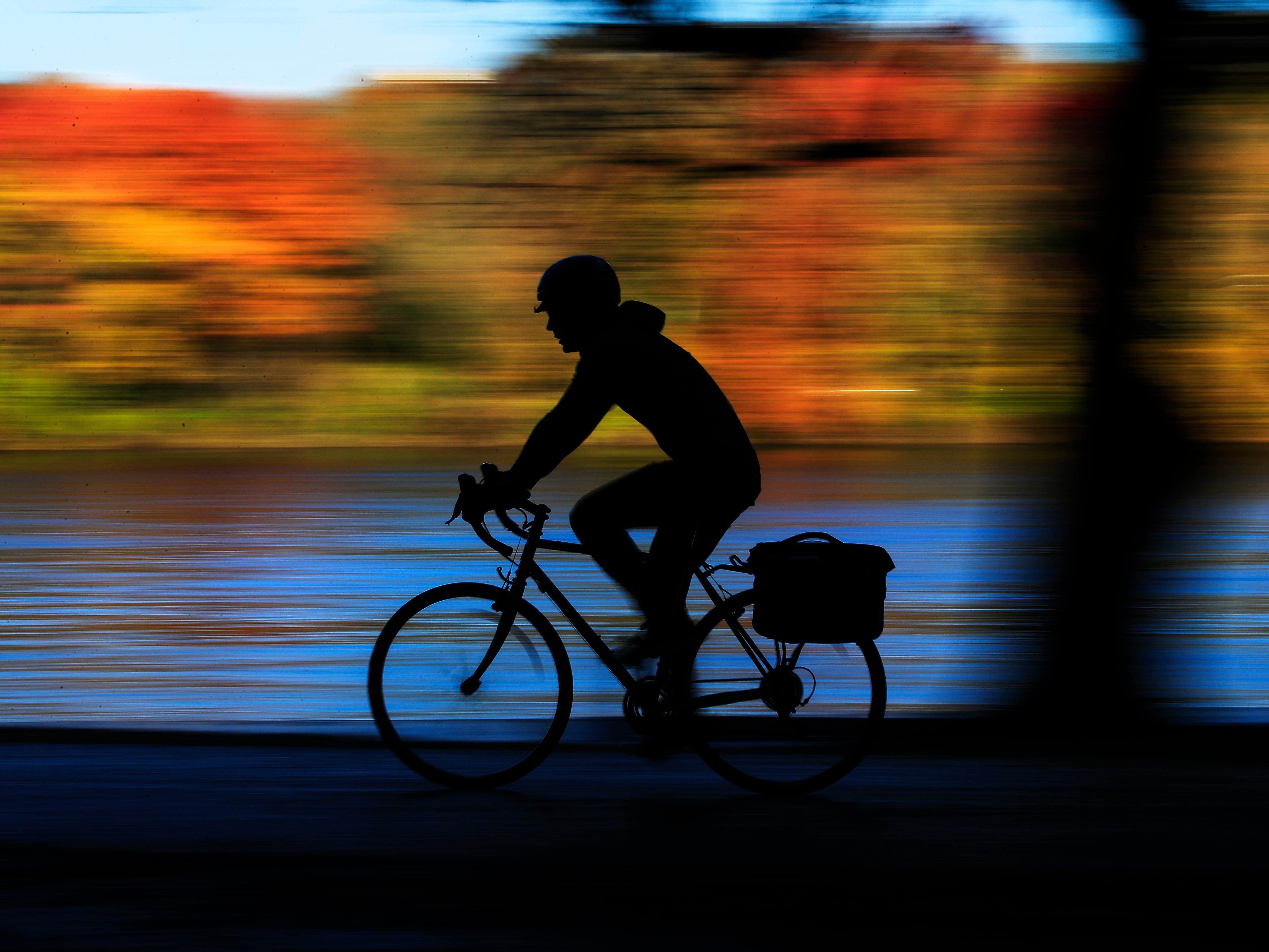 A cyclist makes their way along Kelly Drive on an autumn morning in Philadelphia, Wednesday, Nov. 7, 2018.