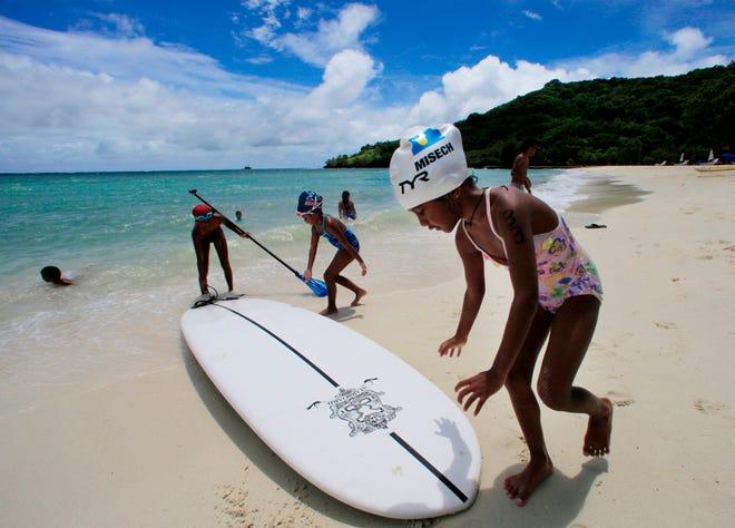 Children play at a resort beach in Ngerkebesang, Palau on June 13, 2009.