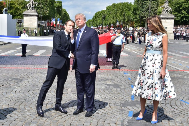 French President Emmanuel Macron  shakes hands with President Donald Trump, next to first lady Melania Trump, during the annual Bastille Day military parade on the Champs-Elysees in Paris in 2017.