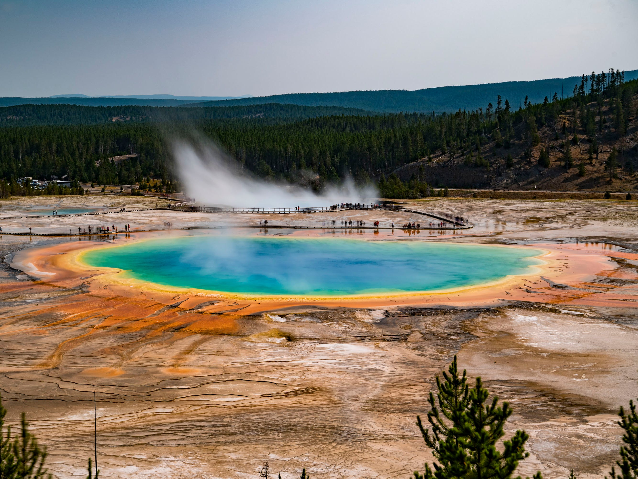 The tour includes a visit to the otherworldly Grand Prismatic Spring with its stunning rainbow of vibrant colors.