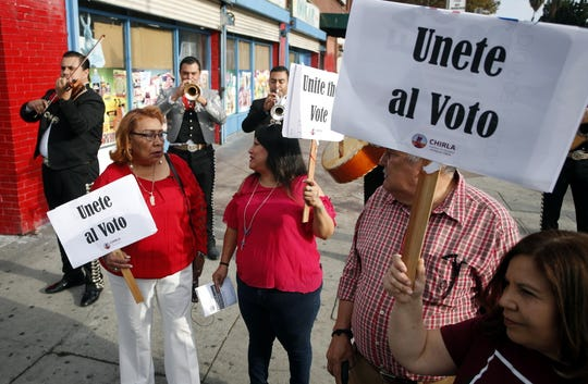"Latino voters Griselda Sanchez (L) and Evelyn Franco (2L) carry signs that read ""Unite the Vote"" as they are serenaded by mariachis on their way to their polling station to cast their ballots in the 2018 midterm general election in Los Angeles, California, Nov. 6, 2018."