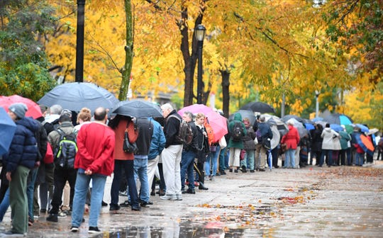 People brave the bad weather and a long line to vote in New York.