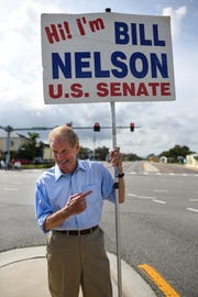 Sen. Bill Nelson, D-Fla., holds his original election sign Nov. 5, 2018, at U.S. 1 and Eau Gallie Boulevard in Melbourne, Florida.