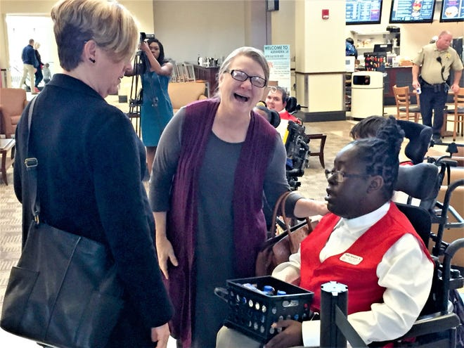 Michael with the Louisiana Special Education Center talks with Melissa Myers of Ferriday (center) and Kim Bravo of Jacksonville, Florida (left) at Alexandria International Airport Thursday. Michael is part of the new Airport Ambassadors program.