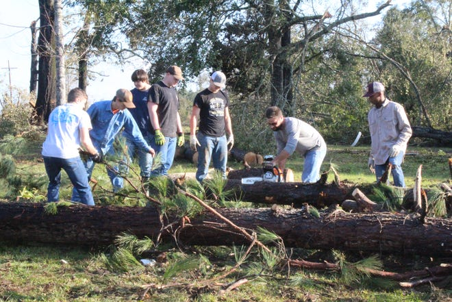 Jena football players and coaches assist in cleaning up storm damage in LaSalle Parish on Tuesday.