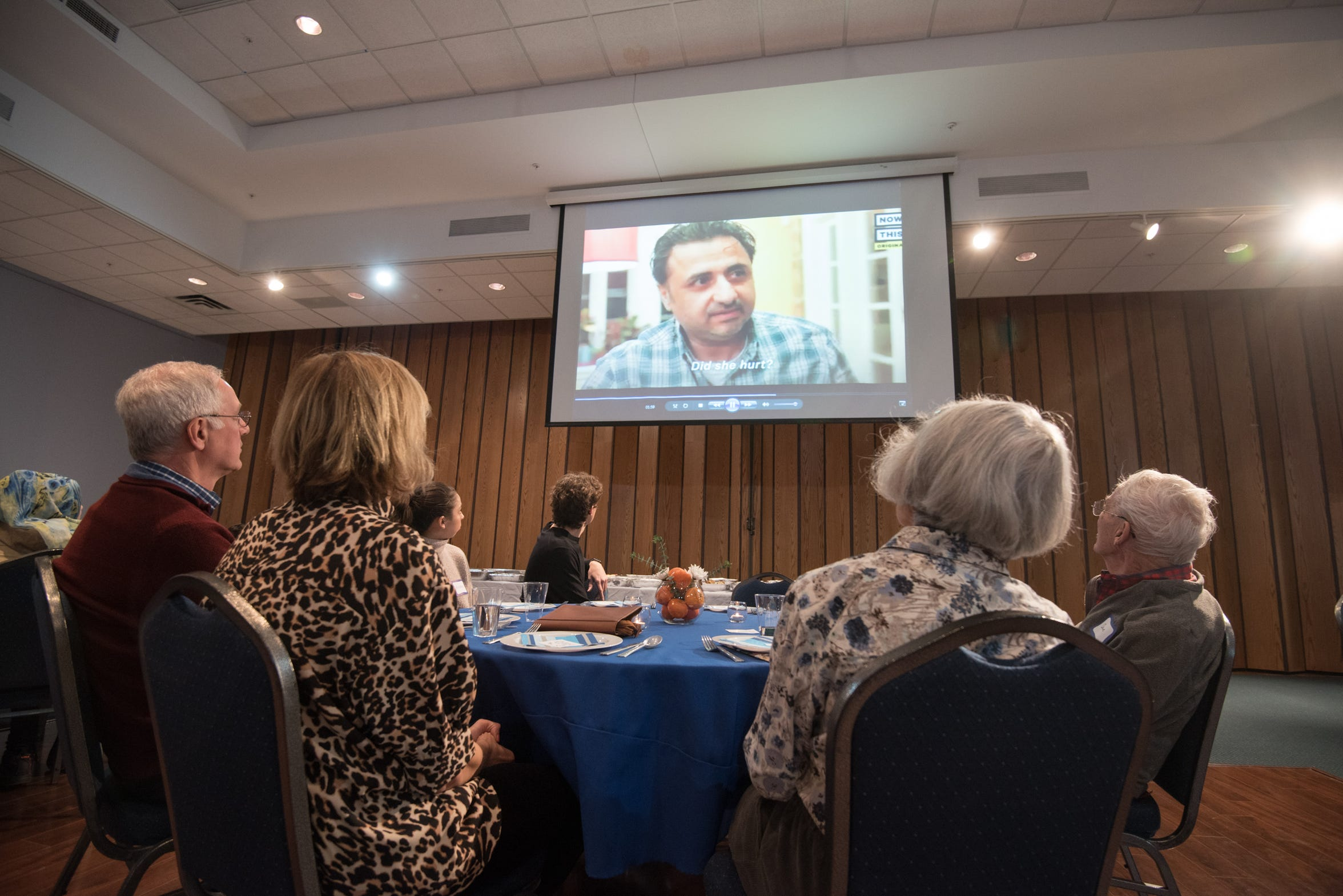 Guests watch a video about Syrian refugees. Members of the Syrian Supper club made dinner for atendees at the Monmouth Reformed Temple in Tinton Falls on Saturday, February 10, 2018. /Russ DeSantis for the Asbury Park Press