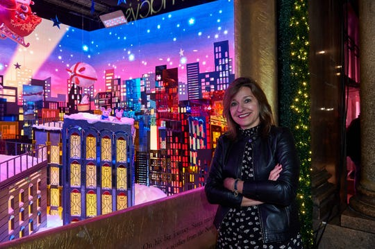 Artist Roya Sullivan with one of her window displays for Macy's.