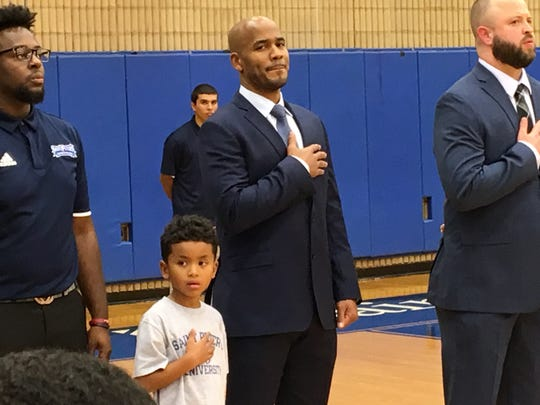 Shaheen Holloway and his 5-year-old son Xavier  during the national anthem prior to his head-coaching debut.