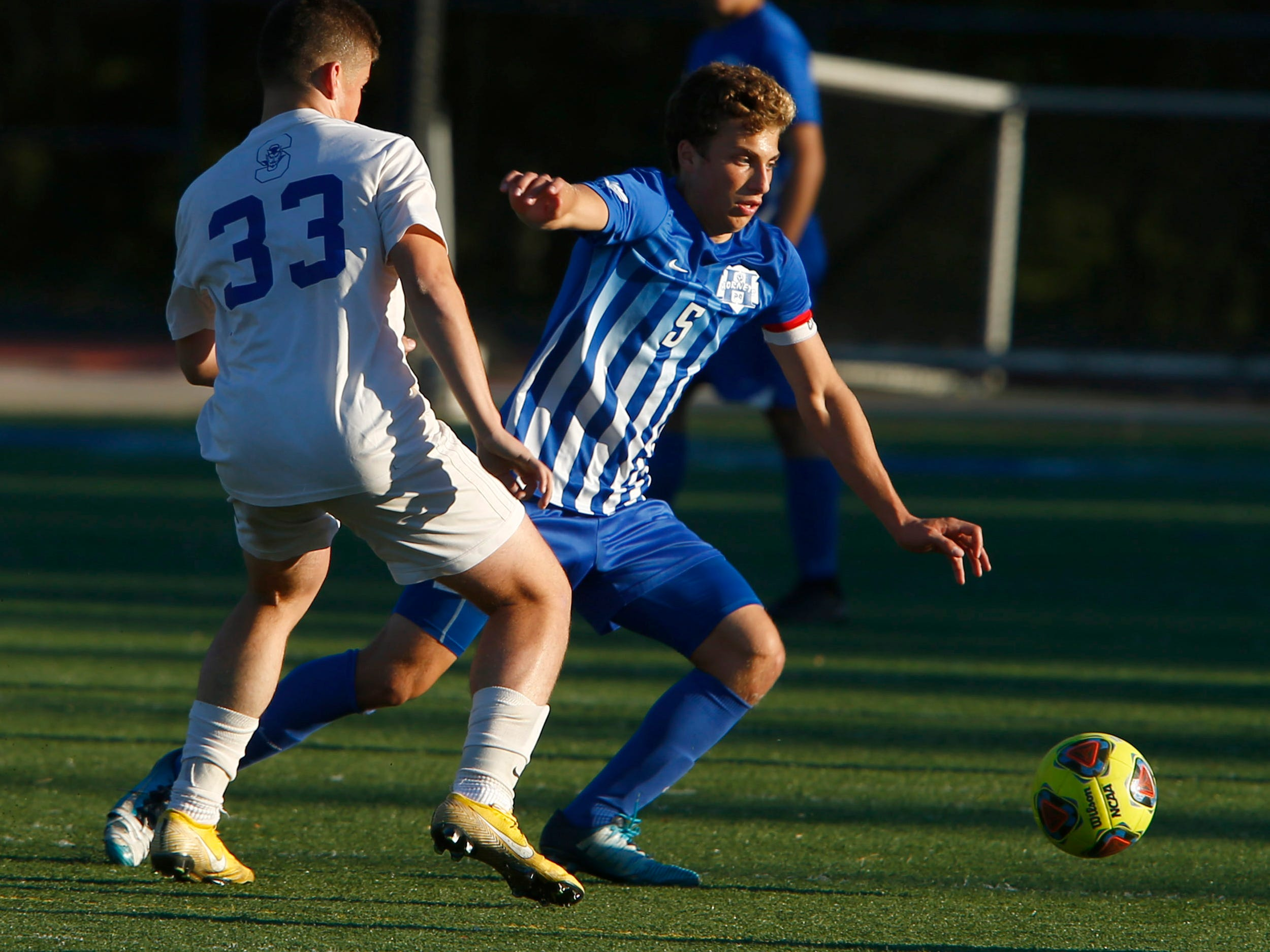 Holmdel's Joe Arena (#5) chases down the ball in front of Shore Regional's Brandon DeNovaes during their Central Group II boys soccer final game played in Holmdel Thursday, November 8, 2018.