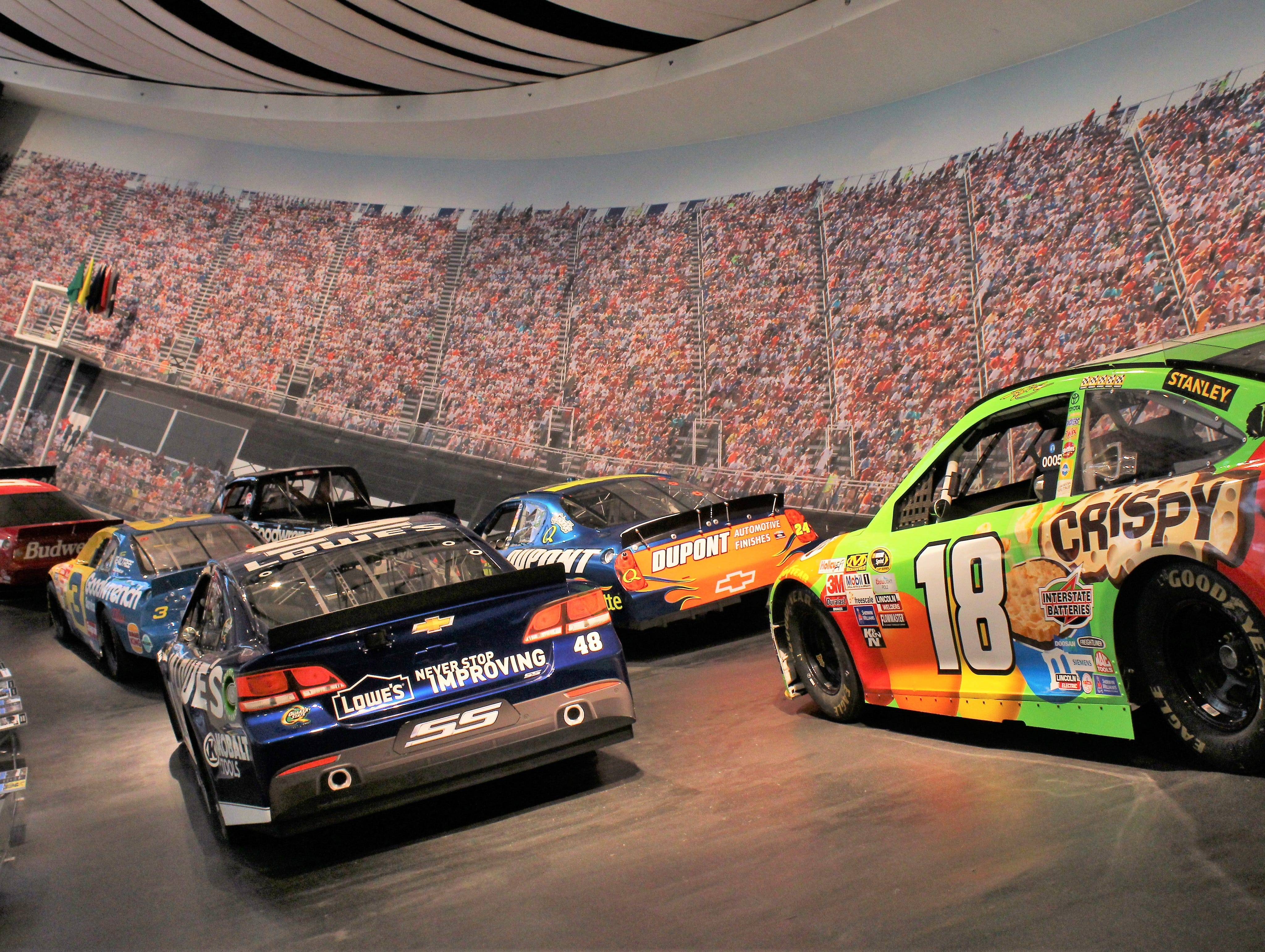 The Glory Road exhibit at the NASCAR Hall of Fame features a display of some of the most iconic cars in the sport on a race track setting.