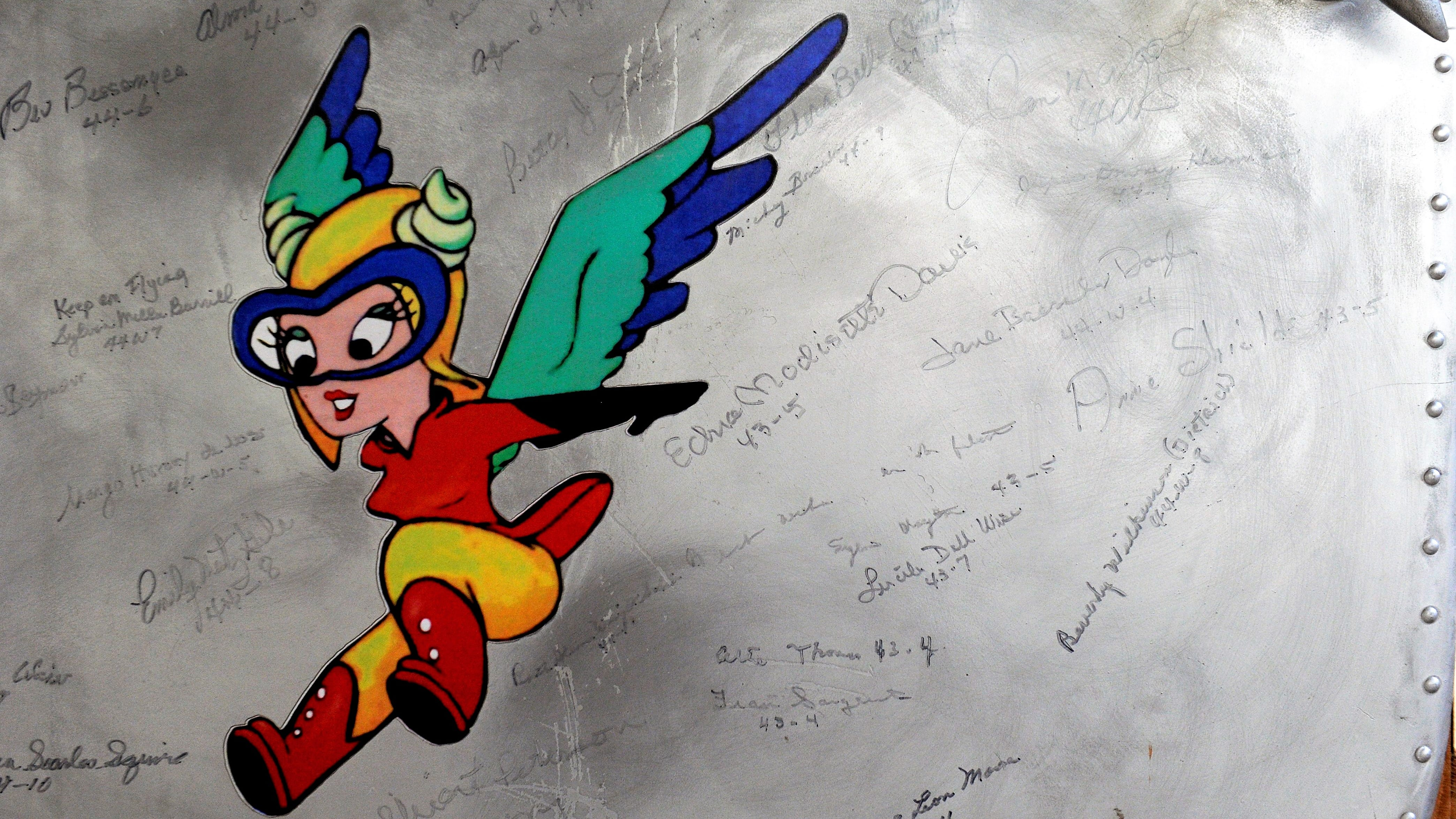 Signatures of past WASPs decorate an aluminum aircraft door around an image of Fifinella, the mascot for the Women's Airforce Service Pilots.